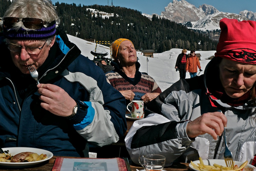 Woman suns while skiers eat at outside tourist restaurant in snowy mountains.