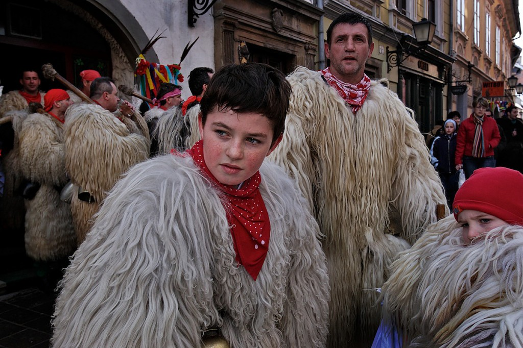 Boys and man wear red scarves and long, white fur attire in the street