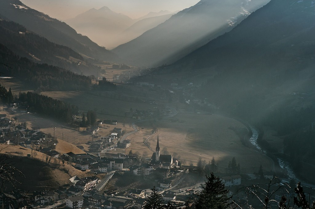 Tiny village with church creates picturesque scene in valley and mountain landscape.