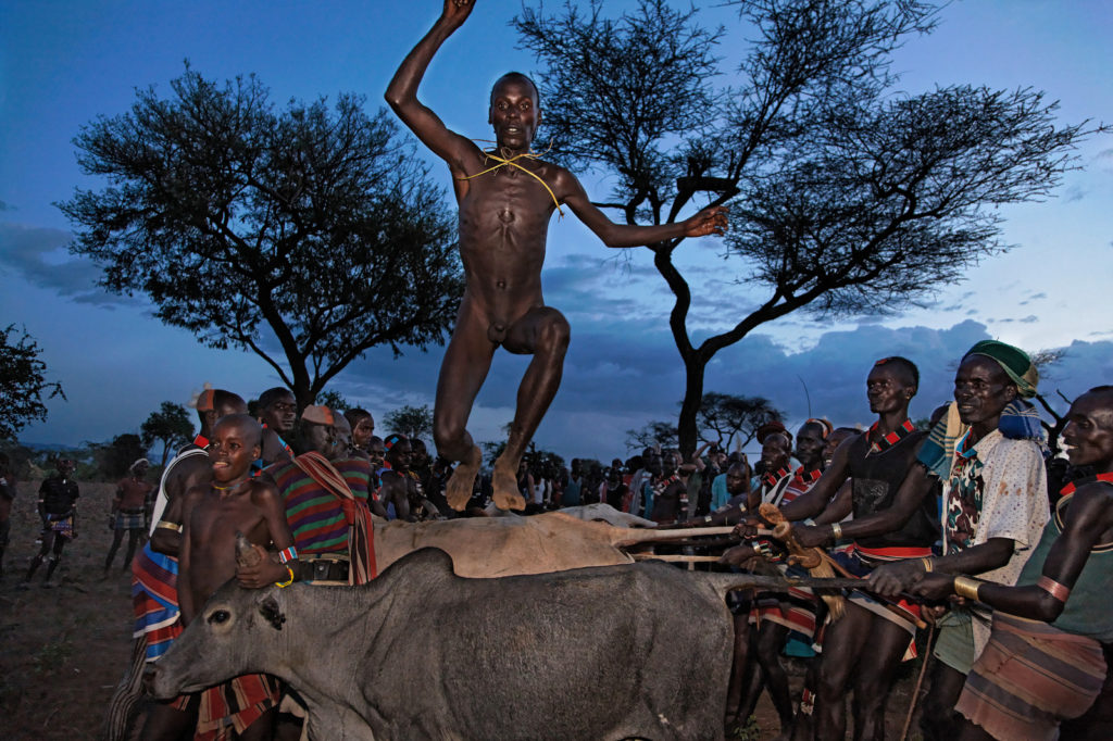 naked man suspended in the air in front of a dark blue sky as he jumps over bulls with others holding them by the tails and horns