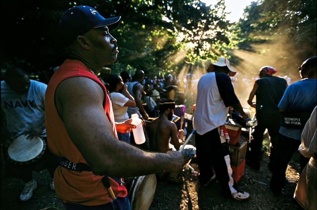 Gathering of African American men playing instruments and drums outside in a woods.