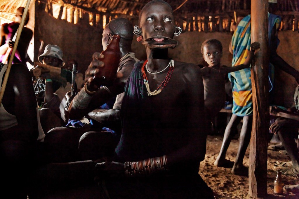 Tribal woman with lip plate licks drops of beer with her tongue in a hut-like bar