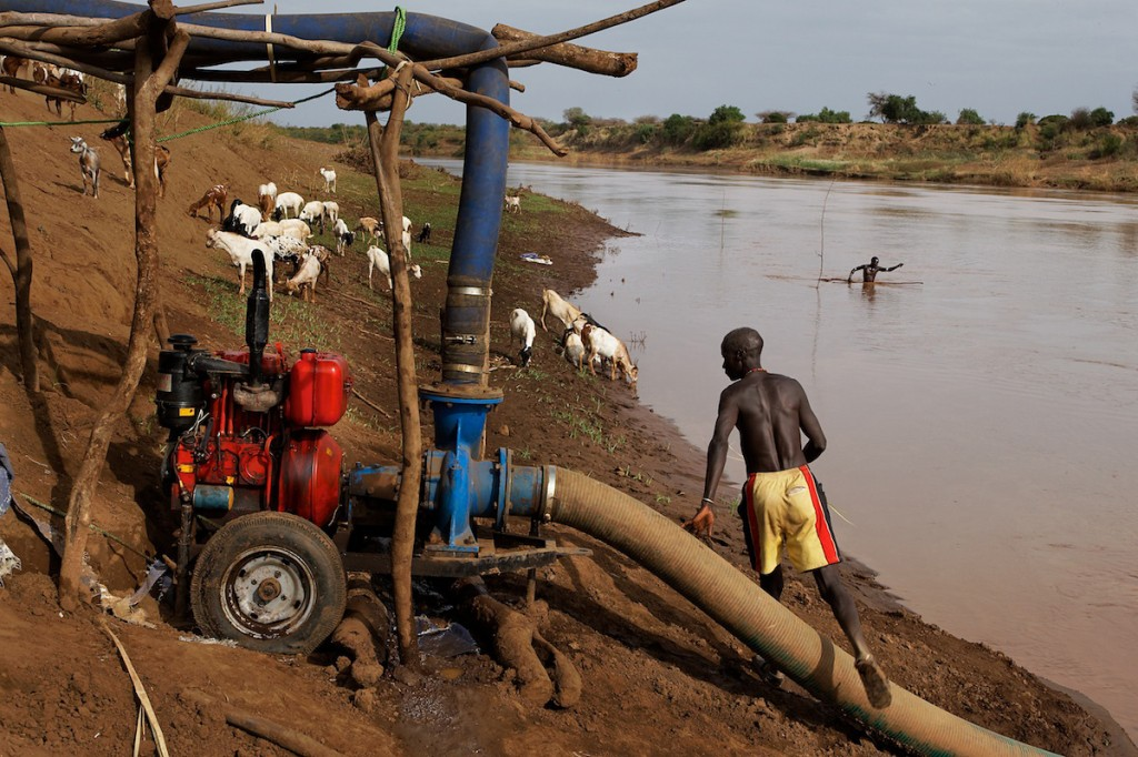 Water pump and pipes along the river with a man working
