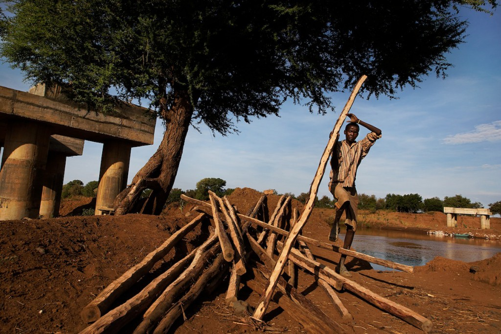 African man carries wood poles at construction site