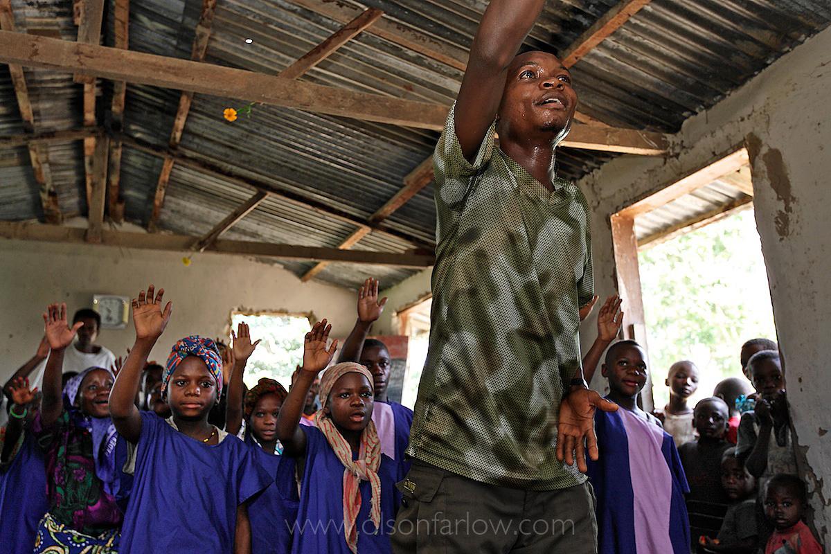 A Bantu organizes a Pygmy choir in a church in Epulu | DR Congo