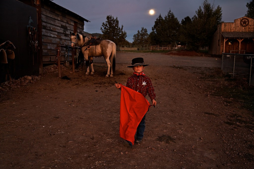 Horse watches as cowboy youth wears sheriff's badge, black hat and holds cape on ranch under full moon.